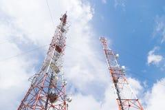 Tour de deux télécommunications un jour ensoleillé contre un ciel bleu Image stock