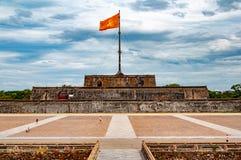 Tour de drapeau en Hue, Vietnam, avec le drapeau communiste et les nuages et les touristes dramatiques dans le forground - vue sy photo libre de droits