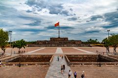 Tour de drapeau en Hue, Vietnam, avec les nuages et les touristes dramatiques dans le forground photographie stock libre de droits