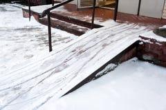 Tour de fauteuil roulant couvert de neige attention Le problème du déblaiement de neige dans la ville Non nettoyé photo libre de droits