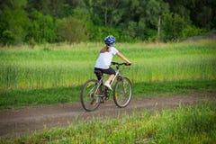 Tour de fille sur le vélo sur le paysage rural Images libres de droits