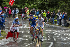 Tour de France Action. Le Markstein, France- July 13, 2014:A fan cheers a group of three cyclists on the road to mountain pass Le Markstein during the stage 9 of Royalty Free Stock Photography
