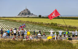 Tour de France landscape. Ardevon,France- July 10, 2013: A cyclists passing through rows of spectators on the roadsides in front of Le Mont Saint Michel Royalty Free Stock Images
