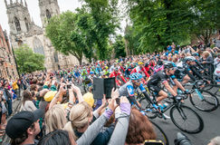 Tour de France peleton in York. York, United Kingdom – July 6, 2014: People watch the Tour de France peleton riding past York Minster in York, UK.The Tour De Stock Photos