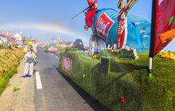 Tour de France Rainbow. Ardevon, France- July 10, 2013: A truck advertising Vittel water spray the fans and generate a rainbow during the passing of the Stock Image