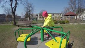 Tour de main de père vilain petite fille sur l'oscillation colorée dans le terrain de jeu de parc de ville banque de vidéos