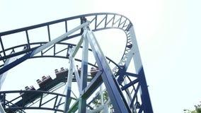 Tour de montagnes russes fonctionnant en parc d'attractions Montagnes russes extr?mes en mouvement d'attraction au parc d'attract banque de vidéos