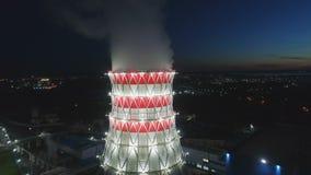 Tour de refroidissement de vue aérienne à la lumière de projecteur et à la ville foncée banque de vidéos