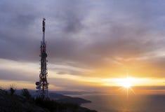 Tour de télécommunication avec le soleil au-dessus de la mer Image libre de droits