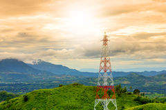 Tour de télécommunication pendant le fond de montagne de coucher du soleil dans le rai Photographie stock libre de droits