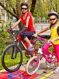 Tour de vélo de famille avec le sac à dos faisant un cycle sur la ruelle de vélo Photographie stock libre de droits