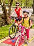 Tour de vélo de famille avec le sac à dos faisant un cycle sur la ruelle de vélo Photos libres de droits