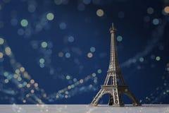 Tour Eiffel de souvenir sur un fond bleu-foncé avec le bokeh coloré s'allume Image stock
