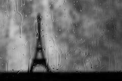 Tour Eiffel vu par la fenêtre humide dans la tempête de pluie images stock