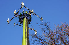 Tour en acier de télécommunication avec des antennes au-dessus de ciel bleu et d'arbres Image stock