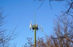 Tour en acier de télécommunication avec des antennes au-dessus de ciel bleu et d'arbres Photos libres de droits