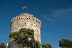 Tour en pierre antique avec le drapeau grec sur le dessus Image stock