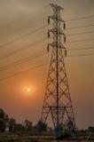 Tour et ligne électrique à haute tension de courrier sur le fond de ciel de coucher du soleil Photos libres de droits