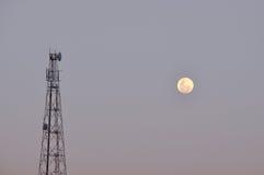 Tour et lune de relais de boîte de vitesses de Telco en soirée Photos libres de droits