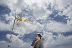 Tour et nuages satellites d'Using Cellphone Against d'homme d'affaires Photographie stock