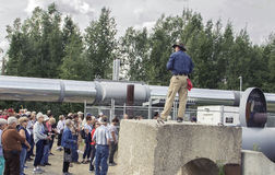 Tour Group Listens to Spiel at Epicenter of Alaska Pipeline royalty free stock images