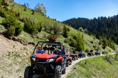 A tour group travels on ATVs and UTVs on the mountains Stock Images