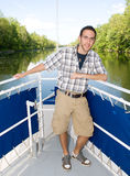 Tour guide man. One young adult male with glasses on the front of a boat giving a tour during a river journey Royalty Free Stock Images