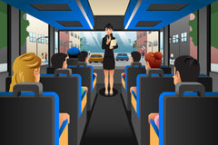 Tour guide talking to tourists in a tour bus stock illustration