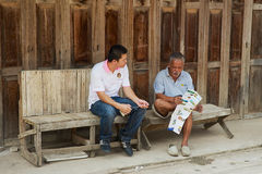 Tour guides sit at the entrance to one of the hostels in Chiang Khan, Thailand. Royalty Free Stock Photos