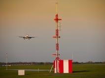 Tour hertzienne d'aéroport et avion d'atterrissage de terre Image stock