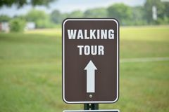 Walking Tour Path Guide Sign. A tour is a long journey including the visiting of a number of places in sequence, especially with an organized group led by a royalty free stock photos