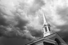 Tour noire et blanche de Steeple d'église au-dessous de Thunde orageux sinistre photo libre de droits