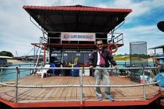 Tour operator Seri Gawi Houseboat, Terengganu. Tour operator Encik Bakar an owner of Seri Gawi Houseboat posing with large  80 footer steel Pontoon Boathouse Royalty Free Stock Images