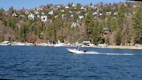 Motoboat on lake arrowhead mountain lake resort. Speed boat passing by celebrities estates on mountain lake resort in Lake Arrowhead California. Boating and stock video footage