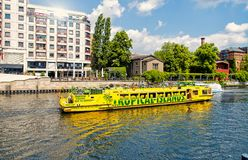 Tour by river on yellow boat with tourists. Berlin, Germany - May 31, 2017: tour by river on yellow boat with tourists along city canal on skyline background royalty free stock photos