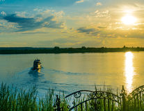 Tour ship sailing at sunset. Tour ship in still waters leaving marshy banks at sunset Stock Photos