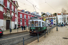 Tour tram on the streets of Alfama, Lisbon`s oldest and most traditional neighborhood. LISBON - CIRCA MARCH 2017: Tour tram on the streets of Alfama, Lisbon`s royalty free stock photography