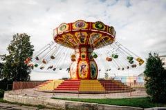 Tourbillon de carrousel en parc contre un ciel nuageux photographie stock