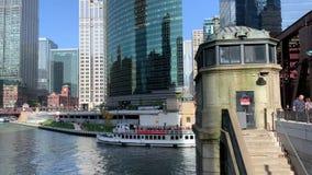 Tourboat пересекает под мостом улицы озера где регулярные пассажиры пригородных поездов спешат и бега поезда el на следе над Реко сток-видео