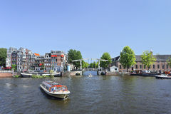 Tourboat with ancient bridge and houses on background. Stock Photo