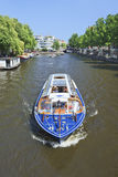 Tourboat in a canal, Amsterdam center Stock Photography