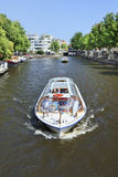 Tourboat in a canal, Amsterdam center Stock Photo