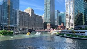Tourboat and water taxi pass each other while tourists paddle kayaks during evening commute on Chicago River. Tourboat and water taxi pass each other while stock video footage