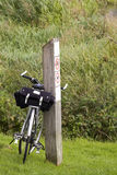 Touring bicycle. Leaning against wooden post Royalty Free Stock Image