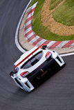 Touring car on track. Fast moving touring car speeding around the track stock photo