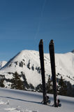 Touring skis sticked in the deep fresh snow with m Stock Photo