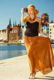 Beautiful elegant woman taking pictures with camera. Tourism, artistic, elegant fashion. Beautifully dressed in sun hat and long dress woman taking pictures Stock Image