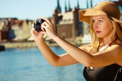 Beautiful elegant woman taking pictures with camera. Tourism, artistic, elegant fashion. Woman in elegant outfit and sun hat taking pictures Royalty Free Stock Image