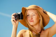 Beautiful elegant woman caught on taking pictures. Tourism, artistic, elegant fashion. Woman in elegant outfit and sun hat taking pictures with one eye closed Royalty Free Stock Photography