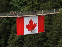 Tourism in Canada: Capilano Suspension Bridge with Canadian Flag Royalty Free Stock Photo